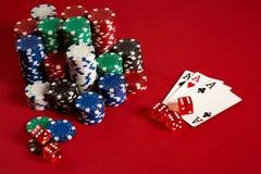Concetto di gioco dell'attrezzatura e di spettacolo del poker del casinò - vicino su delle carte da gioco e dei chip a fondo ross Fotografie Stock Libere da Diritti