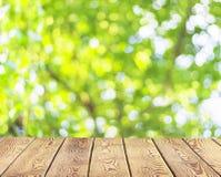 Concetto di Giornata mondiale dell'ambiente: Tavola di legno vuota sopra l'albero vago con il fondo del bokeh fotografia stock