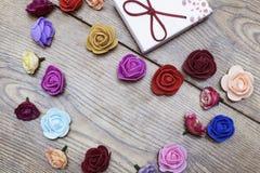 Concetto di giorno degli amanti Il contenitore di regalo con il gruppo di cuore ha modellato le rose sulla tavola di legno Vista  fotografia stock