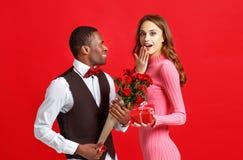 Concetto di giorno del ` s del biglietto di S giovani coppie felici con cuore, fiori, regalo su rosso fotografie stock libere da diritti