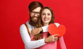 Concetto di giorno del ` s del biglietto di S giovani coppie felici con cuore, fiori, regalo su rosso immagine stock