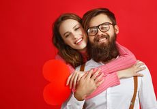 Concetto di giorno del ` s del biglietto di S giovani coppie felici con cuore, fiori, regalo su rosso fotografie stock
