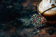 Concetto di giorno del ` s del biglietto di S. Valentino - pendente dei gioielli del cuore su fondo nero Fotografie Stock