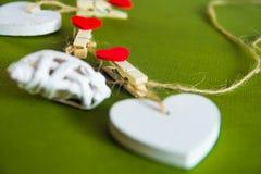 Concetto di giorno del ` s del biglietto di S Cuori di legno bianchi riparati con le mollette da bucato su cavo su fondo verde Fotografie Stock Libere da Diritti
