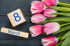 Concetto di giorno del ` s delle donne I tulipani rosa e l'8 marzo datano su fondo blu Fotografie Stock