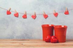 Concetto di giorno di biglietti di S. Valentino con le forme rosse delle tazze e del cuore di caffè Immagine Stock