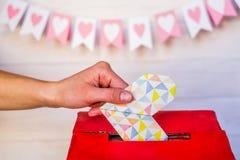 Concetto di giorno di S mano femminile che mette il cuore di origami ad una scatola rossa del biglietto di S. Valentino Fotografia Stock Libera da Diritti