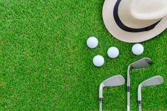 Concetto di golf: Il cappello di Panama, le palle da golf, ferro del golf bastona la disposizione del piano Immagine Stock