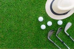 Concetto di golf: Il cappello di Panama, le palle da golf, ferro del golf bastona la disposizione del piano Immagini Stock