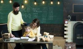 Concetto di graduazione Genitori con il bambino in cappuccio di graduazione allo scrittorio Classe di graduazione in scuola eleme Immagine Stock