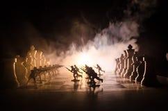 Concetto di guerra Siluette dei soldati sulla scacchiera Concetto di guerra Siluette militari che combattono scena sul fondo del  Fotografie Stock