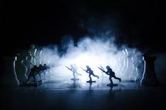 Concetto di guerra Siluette dei soldati sulla scacchiera Concetto di guerra Siluette militari che combattono scena sul fondo del  Fotografie Stock Libere da Diritti