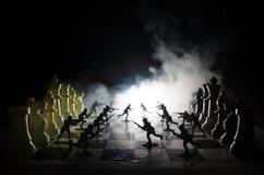 Concetto di guerra Siluette dei soldati sulla scacchiera Concetto di guerra Siluette militari che combattono scena sul fondo del  Fotografia Stock Libera da Diritti