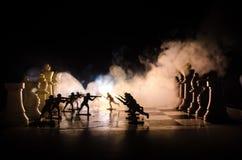 Concetto di guerra Siluette dei soldati sulla scacchiera Concetto di guerra Siluette militari che combattono scena sul fondo del  Fotografia Stock