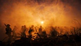 Concetto di guerra Siluette militari e carri armati che combattono scena sul fondo del cielo della nebbia di guerra, siluette dei Immagini Stock
