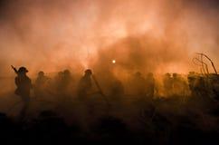Concetto di guerra Siluette militari e carri armati che combattono scena sul fondo del cielo della nebbia di guerra, siluette dei Fotografie Stock