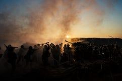Concetto di guerra Siluette militari e carri armati che combattono scena sul fondo del cielo della nebbia di guerra, siluette dei Fotografia Stock