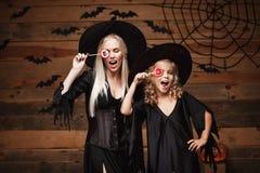 Concetto di Halloween - bella madre caucasica e sua la figlia in costumi della strega che celebrano Halloween con la caramella di Fotografie Stock Libere da Diritti