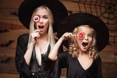 Concetto di Halloween - bella madre caucasica e sua la figlia in costumi della strega che celebrano Halloween con la caramella di Fotografie Stock