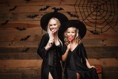 Concetto di Halloween - bella madre caucasica e sua la figlia in costumi della strega che celebrano Halloween con la caramella di Fotografia Stock