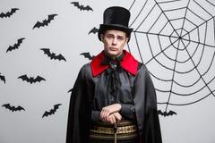 Concetto di Halloween del vampiro - ritratto del vampiro caucasico bello in costume nero e rosso di Halloween immagini stock