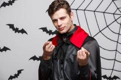 Concetto di Halloween del vampiro - ritratto del vampiro caucasico bello in costume nero e rosso di Halloween fotografia stock libera da diritti