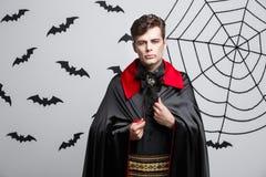 Concetto di Halloween del vampiro - ritratto del vampiro caucasico bello in costume nero e rosso di Halloween immagine stock