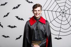 Concetto di Halloween del vampiro - ritratto del vampiro caucasico bello in costume nero e rosso di Halloween fotografia stock