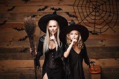 Concetto di Halloween - la madre allegra e sua la figlia in costumi della strega che celebrano Halloween che fa il silenzio gestu Fotografia Stock Libera da Diritti