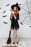 Concetto di Halloween - la strega elegante felice gode di di giocare con il partito di Halloween del manico di scopa sopra fondo  Fotografie Stock