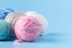 Concetto di hobby del cucito Bugne della lana su fondo blu Immagini Stock