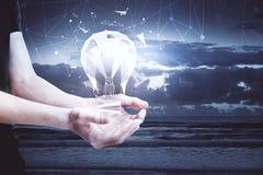 Concetto di idea con la lampadina in mani Immagine Stock