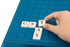 Concetto di IMPOSTA di GST con le parole incrociate su un gioco da tavolo Fotografia Stock Libera da Diritti
