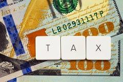 Concetto di imposta - segni l'etichetta con lettere sul fondo dei soldi Fotografia Stock