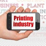 Concetto di industria: Passi la tenuta dello Smartphone con l'industria di stampa su esposizione royalty illustrazione gratis