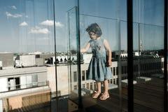 Concetto di infanzia Piccolo ragazza prescolare sveglia sul balcone di vetro fotografia stock