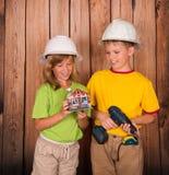 Concetto di ingegneria e del bene immobile Costruttori sorridenti dei bambini i immagini stock