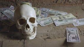 Concetto di ingordigia dei soldi con il cranio umano, il cranio ed i soldi di caduta stock footage