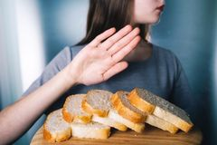 Concetto di intolleranza del glutine La ragazza rifiuta di mangiare il brea bianco Fotografia Stock