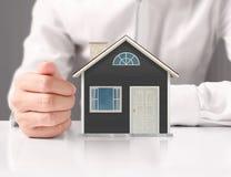 Concetto di ipoteca dalla casa dalla mano Immagine Stock