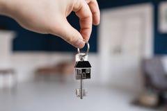 Concetto di ipoteca La chiave della tenuta della mano degli uomini con la casa ha modellato il keychain Interno leggero moderno d Fotografia Stock