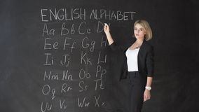 Concetto di istruzione - concetto della lavagna della scuola di alfabeto di ABC Maestro di scuola che scrive alfabeto di ABC nell stock footage