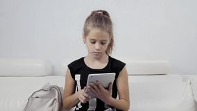 Concetto di istruzione, della scuola, di tecnologia e di Internet - piccola ragazza dello studente con il pc della compressa a sc video d archivio