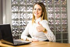Concetto di istruzione, di affari e di tecnologia - donna di affari o studente sorridente che mostra i pollici su con il computer Immagine Stock
