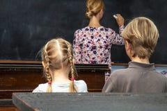 Concetto di istruzione scolastica di scuola primaria pubblica con il giovane ragazzo e la ragazza che ascoltano l'insegnante femm fotografia stock