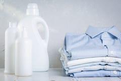 Concetto di lavaggio - mucchio delle camice piegate con la bottiglia del detersivo di lavaggio immagini stock libere da diritti