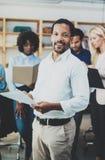 Concetto di lavoro di squadra in ufficio moderno Carte bianche d'uso della tenuta della camicia del giovane uomo d'affari african immagine stock