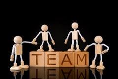 """Concetto di lavoro di squadra, blocchetto di legno del cubo con il  del """"TEAM†di parola e figure di legno gruppo del bastone fotografia stock"""