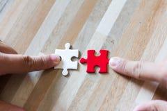 Concetto di lavoro di squadra facendo uso dei pezzi bianchi e rossi di puzzle Immagini Stock