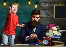 Concetto di lezione di arte L'artista di talento passa il tempo con il figlio L'insegnante con la barba, il padre insegna al picc fotografie stock libere da diritti